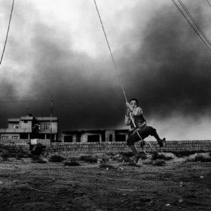 En dreng svinger sig i et elkabel i byen Qayyara i Irak. Foto af Jan Grarup