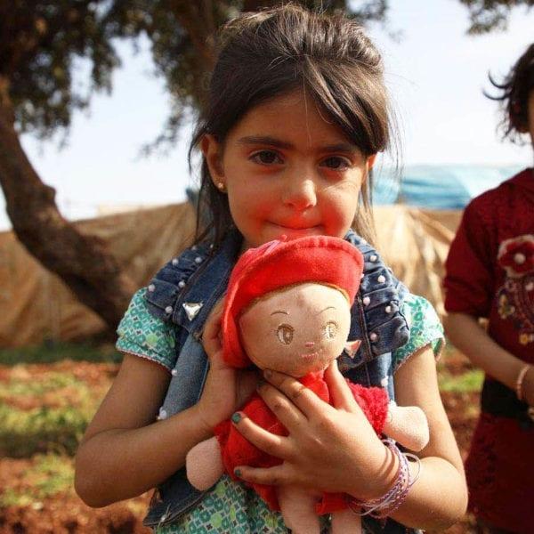 To små iger står foran en lejr i Syrien med en dukke