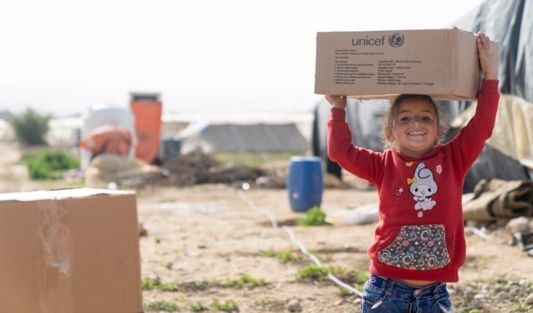 4-årige Sham, som er flygtning fra Syrien, bærer en kasse med vintertøj, som hun har fået af UNICEF