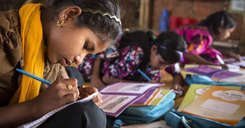 En pige studerer i Bangladesh med nye UNICEF støttet undervisningsmaterialer i et læreingscenter i Camp 18 Kutupalong refugee camp i Cox Bazar.