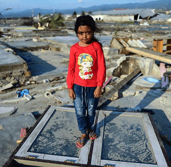 8-årige Marwah Nur Zahra fra Indonesien står midt i ruinerne af sin families hjem, som blev ødelagt af et jordskælv og en efterfølgende tsunami.