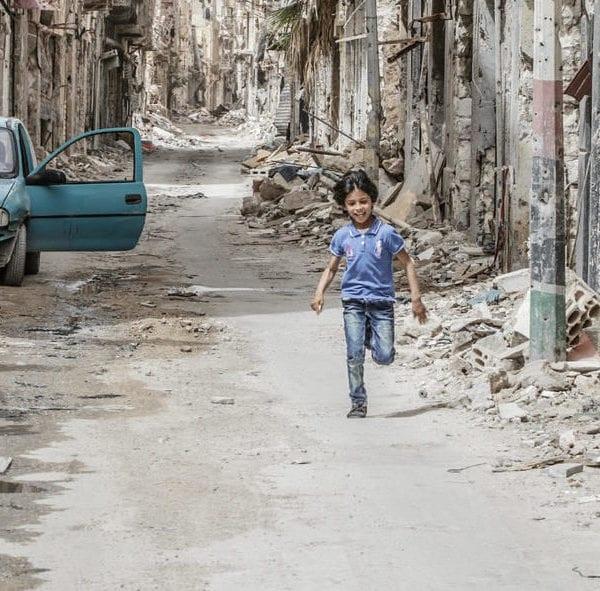 Et barn løber gennem ødelagte gader i Benghazi, Libyen