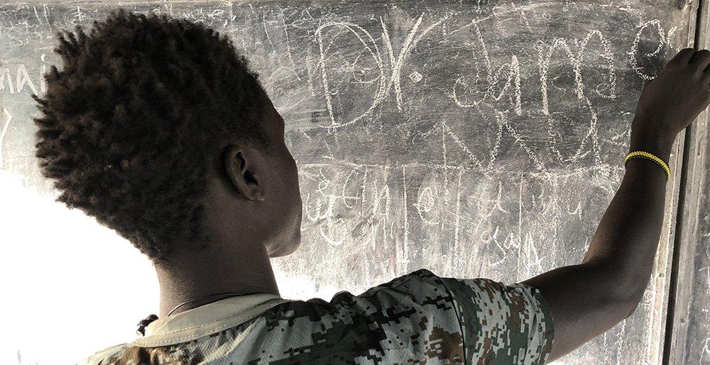 Tidligere børnesoldat James skriver sit navn på tavlen i sit klasselokale