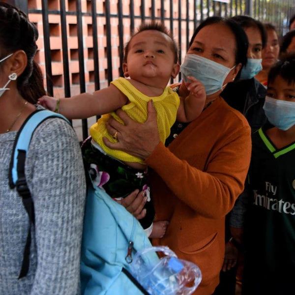 Kvinder og børn bærer masker for at beskytte sig mod corona-virus i Cambodja
